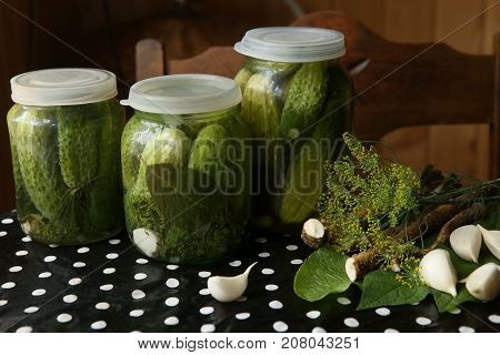 Homemade pickles in glass jars. Pickled cucumbers on table in kitchen. Spices and herbs for making pickles.