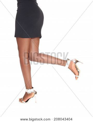 A closeup images of the bottom and legs of a young woman standing in profile with high heels isolated for white background