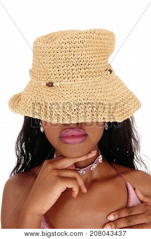 An African woman portrait standing with a straw hat over her eyes and finger under her chin whit big lips isolated for white background