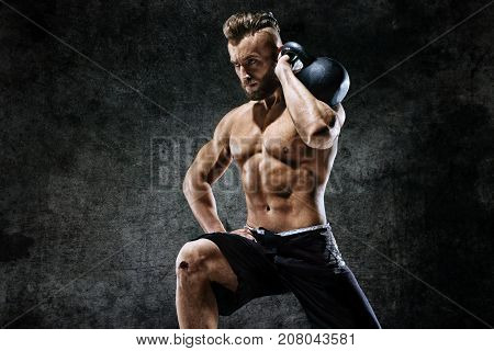 Young man working out with a kettlebell. Photo of man on dark background. Strength and motivation