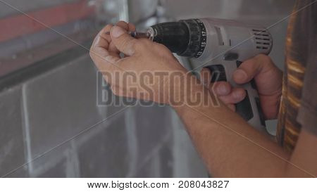 Close up view of cordless electric screwdriver in mans hands. Man attaching drywall.