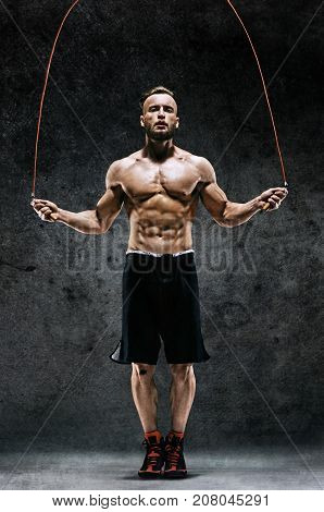 Athletic man skipping with a jump rope on dark background. Best cardio workout