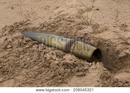 old artillery metal projectile on the sand close-up.