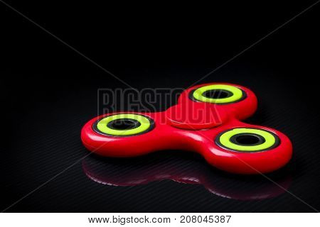 Close-up shot of red-green fidget finger spinner on black gloss background. Antistress and anxiety relief toy.