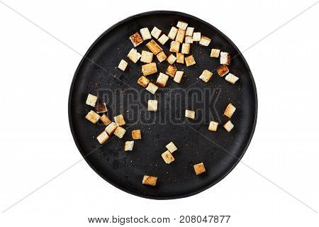 homemade croutons on a cast-iron frying pan isolated
