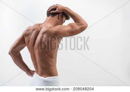Sexy young man is demonstrating his naked trained back. He is touching his head and holding hand on his hip while standing in white towel. Isolated and copy space in right side