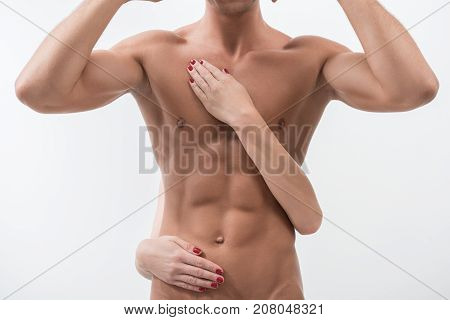 Male perfection. Close-up of muscular sexual body of young man who is posing with hands behind his head. Female hands are touching his torso with tenderness. Isolated background