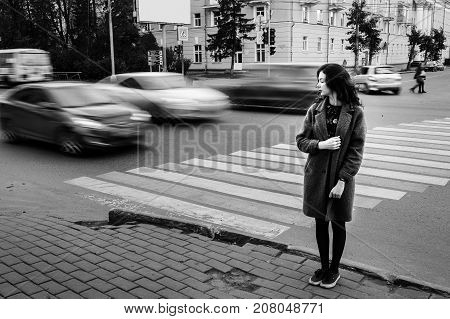 One teenage girl blue coat standing at the traffic light on city street on a cloudly autumn day with vehicles passing by in motion blur. Waiting and time concept.