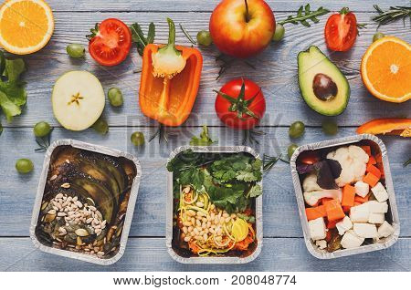 Healthy food delivery, lunch in foil boxes with fresh vegetables on blue wood background. Meals take away and delivery concept.
