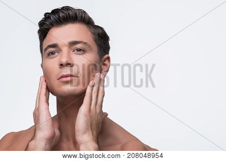 Close-up portrait of seductive young man is standing with naked shoulders. He is looking forward pensively while touching his face sensually. Isolated background with copy space in the right side