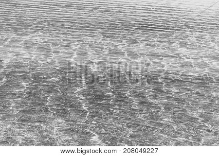 Refraction of light in clear water with small waves. Black and white photo