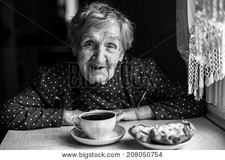 Elderly women drinking tea, black and white contrast portrait.