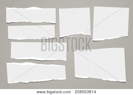 White grainy, spotted ripped note, notebook paper stuck on gray background for your message.
