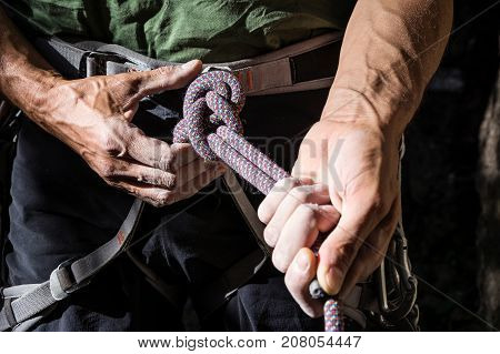 mountain climber tying rope in double bowline knot