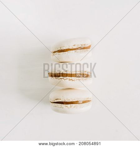 Three pastel macaroons on white background. Flat lay top view macaroon concept.