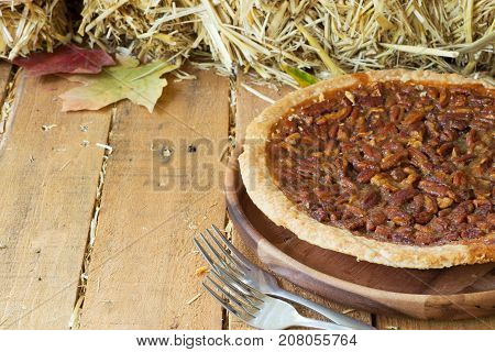 Whole pecan pie on a wooden plate