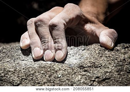 Man's hand climbing on granite. Italian Alps