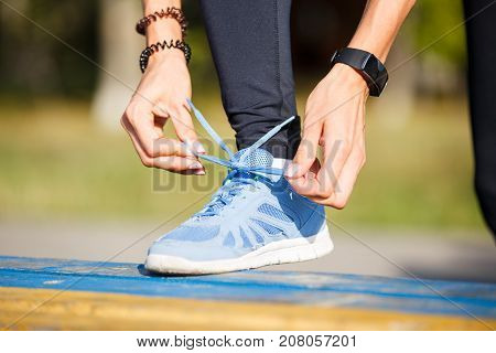 Young woman runner tying shoelaces on the bench.
