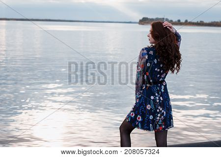 Young beautiful brunette woman in blue dress on the autumn river embankment.