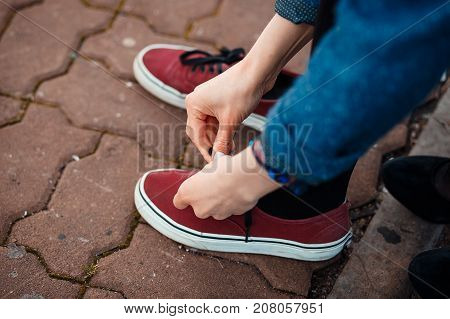 Woman tying shoelace at park. Casual styled sneakers.