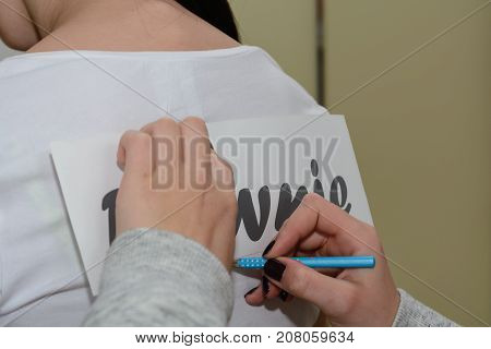 Person prepares text for foli print on a t-shirt