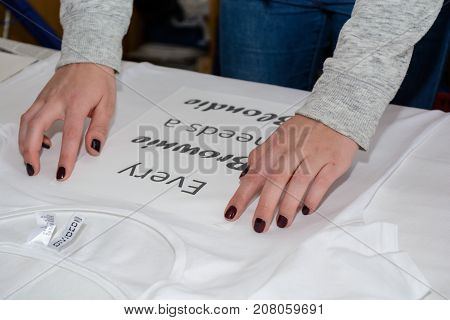 Person aligns text for folio print on iron-on iron t-shirt