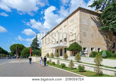 TIRANA ALBANIA - SEPTEMBER 6 2017: Residence of Prime Minister (formerly Central Committee of Communist Party of Albania) on boulevard of Martyrs Tirana Albania. Unknown people walking down street