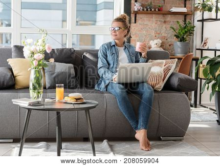 Cheerful lady is sitting on couch and using laptop for work. She looking aside with smile. Copy space on left side