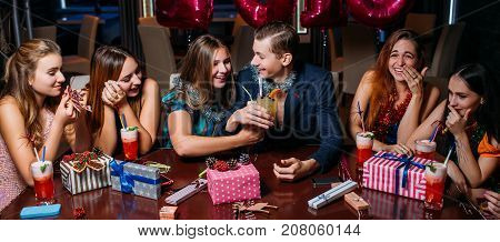 Happy youth Christmas party. Joyful celebration. Young couple drinking brotherhood, smiling friends company. Night club background, New Year concept