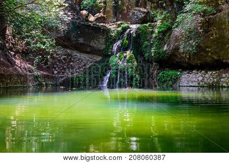 Green lake with small waterfall in Butterfly valley on Rhodes island, Greece