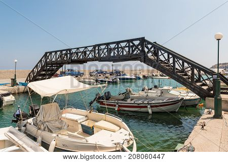 RHODES, GREECE - AUGUST 2017: Small sea port with moored fishing boats under the bridge  on Rhodes island, Greece