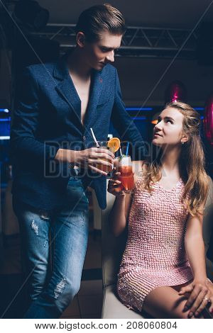 Flirty relationships. Night club party background. Modern stylish youth, romantic atmosphere with drinks, seduction concept