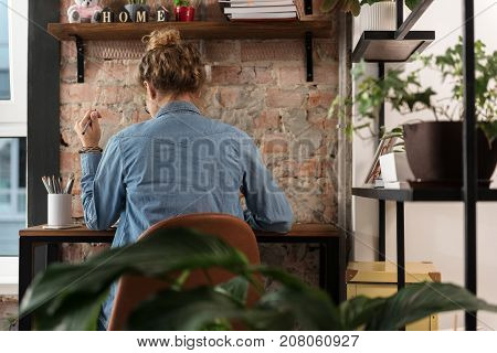 Do not disturb. Busy girl is siting at working desk and holding pen. Focus on female back. Copy space on right side