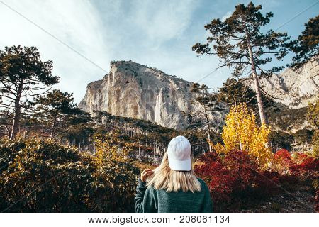 Back view of traveler hipster girl wearing cap and sweater standing alone in autumn woods and looking at mountain hill. Cold weather, fall colors. Wanderlust concept.