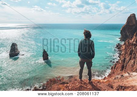 Back view of man traveler standing on mountain alone and looking at autumn sea landscape. Hiking in cold season. Wanderlust concept scene.