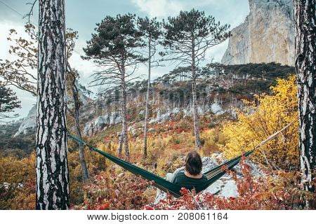 Back view of traveler man hiking and relaxing in hammock in autumn woods and looking at mountain hill. Cold weather, fall colors. Wanderlust concept.