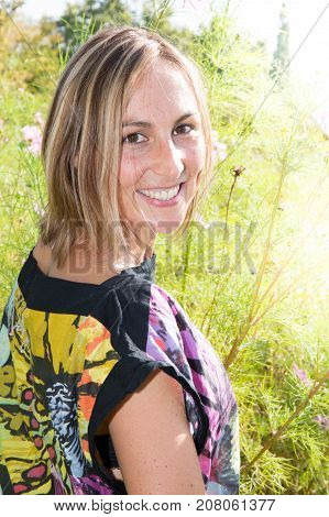 Portrait Of Young Woman In Park With Sun And Flowers