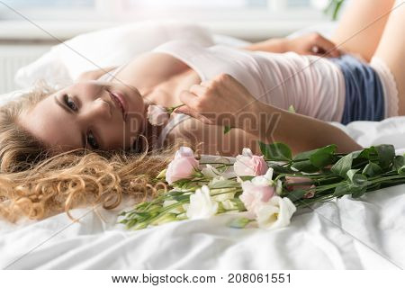 Glad girl is lying on bed and looking at camera with affable smile. She holding flower. Portrait