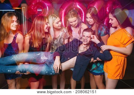 Macho at New Year party. Sexual hints, lustful female company. Seductive young male, funny background, seduction and pickup concept