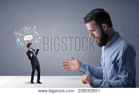 Young professional businessman being angry with an other miniature businessman who has drawn speech and thought bubbles above his head