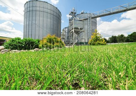 Large modern granary. Sunny day, the blue sky. In the foreground there is a luscious green lawn grass.