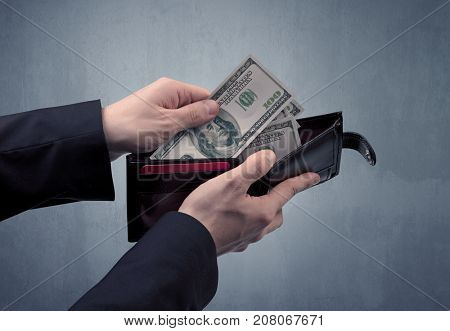 Businessman's hand in suit takes out dollar money from a wallet