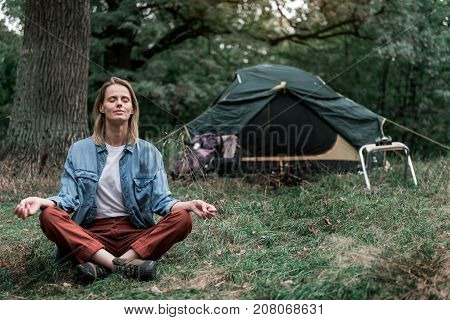 Enjoying peace in nature. Full length portrait of calm young woman meditating in forest. She is sitting in lotus position with closed eyes. Tent on background