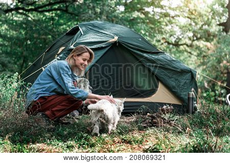 My best friend. Excited female tourist is stroking her puppy with love. She is kneeling near tent in forest and smiling