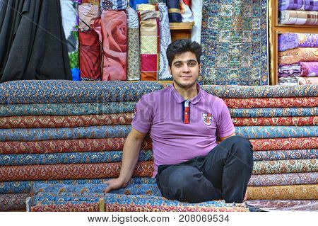 Fars Province Shiraz Iran - 19 april 2017: One young Iranian male salesman is sitting in front of his goods in a fabric store.