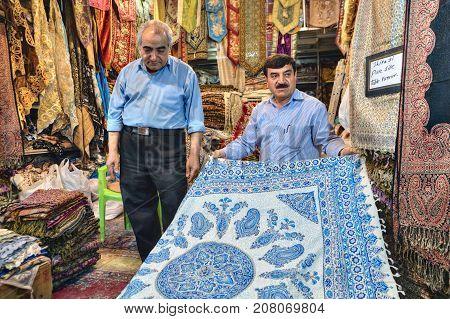 Fars Province Shiraz Iran - 19 april 2017: Decorative textiles department at the city market the Iranian dealer shows his wares.