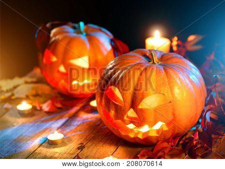 Halloween pumpkin head jack lantern with burning candles over wooden background. Halloween holidays art design, celebration. Carved Halloween Pumpkins with burning candles close up art design
