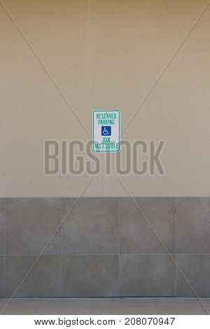 Handicap symbols on road and wall parking place reserved for disabled person.