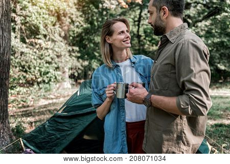 I am so happy with you. Cute young woman is looking at man with love and smiling. They are enjoying tea in the nature together and embracing