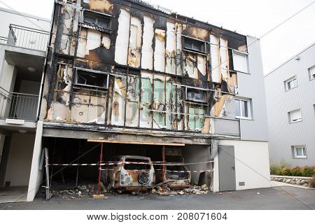Cars After A Fire With Burnt Building